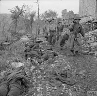Allied soldiers carry a dead comrade from the rubble of Monte Cassino, shortly after the abbey finally fell to Polish troops on May 18, 1944. Dead German defenders, including one stripped of his hobnail boots, lie along the trail.