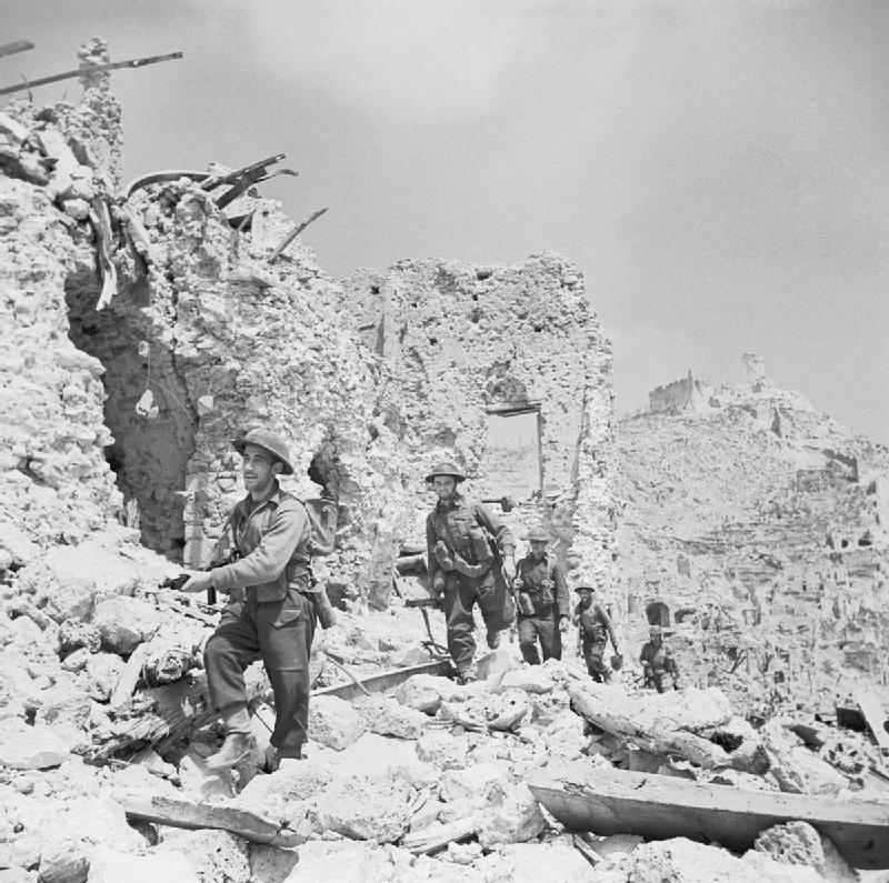 <p class='eng'>Men of the Durham Light Infantry advance through the ruins of Cassino, passing the remains<br /> of the Hotel Des Roses. Tanner (Capt). © IWM (NA14999)</p>